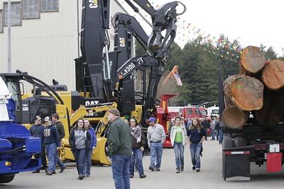 Shaun Walker — The Times-Standard  Visitors walk past logging trucks and heavy equipment.