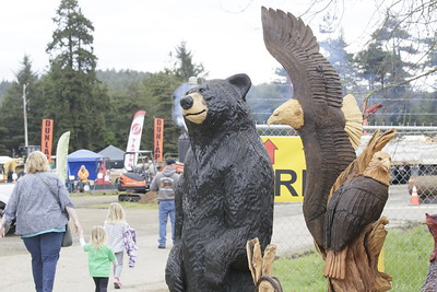 Shaun Walker — The Times-Standard  Visitors walk past finished chainsaw carvings.