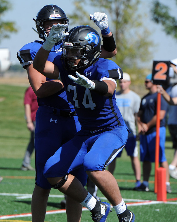 . Resurrection Christian\'s Daniel Kelley (34) and Zane Zuhlke celebrate a touchdown during a game against The Classical Academy on Saturday, Sept. 15, 2018 at Loveland Sports Park. (Sean Star/Loveland Reporter-Herald)