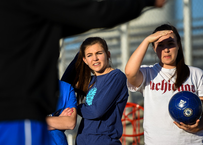 Resurrection Christian girls soccer players listen to coach Randy Wolf as he instructs them during practice Tuesday March 6, 2018 at RCS. (Cris Tiller / Loveland Reporter-Herald)