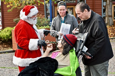 Santa Claus hands Kathleen Thornton a holiday sweet as Nick Arnot and David Arnot stand beside. José Quezada—For Times-Standard