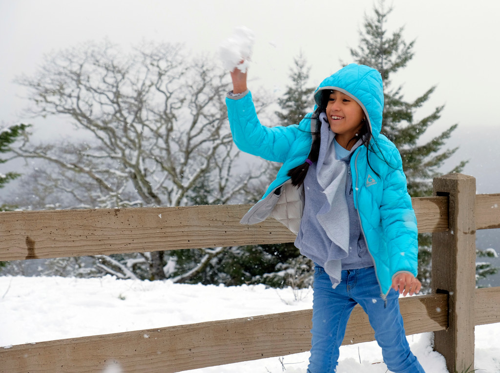 . Shaun Walker � The Times-Standard  Gisselle Mendoza, 8, of Stockton throws a snowball at her dad at the scenic viewpoint near Berry Summit on Highway 299 on Friday. Substantial snow was still predicted through roughly 10 a.m. Sunday near the summit.