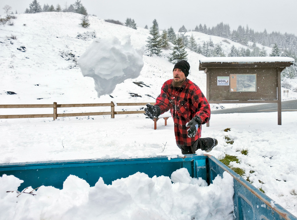 . Shaun Walker � The Times-Standard  Roy Smith Jr of McKinleyville throws a very large snowball into the back of a pick up at Berry Summit along Highway 299 on Friday afternoon so that he could build a snowman in the front yard back on the coast. Substantial snow was still predicted through roughly 10 a.m. Sunday near the summit.