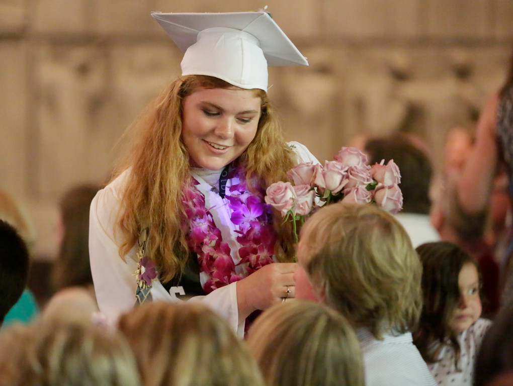 . Shaun Walker � The Times-Standard  St. Bernard\'s Academy senior Reve Tomlin hands out roses at the Eureka school\'s graduation ceremony on Saturday. The private Catholic school graduated 48 students.