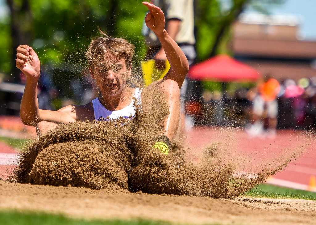. Mountain View\'s Haden Marr crashes into the sand of the triple jump pit at the 2018 state track and field meet Thursday May 17, 2018 at Jeffco Stadium in Lakewood. (Cris Tiller / Loveland Reporter-Herald)