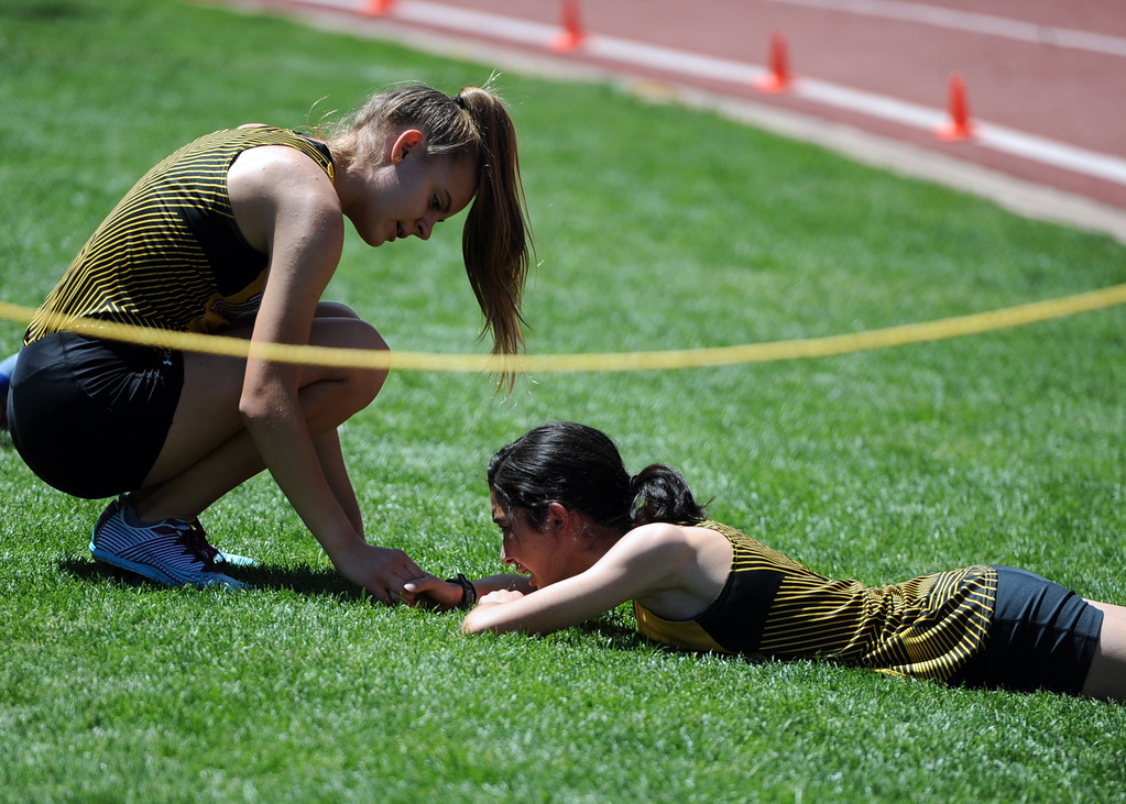 . Thompson Valley\'s Kenadi Krueger lends a hand to teammate Autumn Zhou during the 4x800 relay at the 2018 state track and field meet on Thursday, May 17, 2018 at Jeffco Stadium in Lakewood. (Sean Star/Loveland Reporter-Herald)