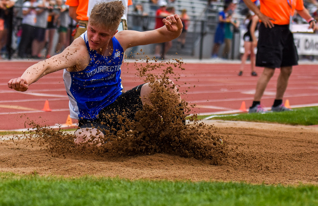 . Resurrection Christian\'s Tanner Applebee splashes the sand in the long jump pit at the 2018 state track and field meet Thursday May 17, 2018 at Jeffco Stadium in Lakewood. (Cris Tiller / Loveland Reporter-Herald)