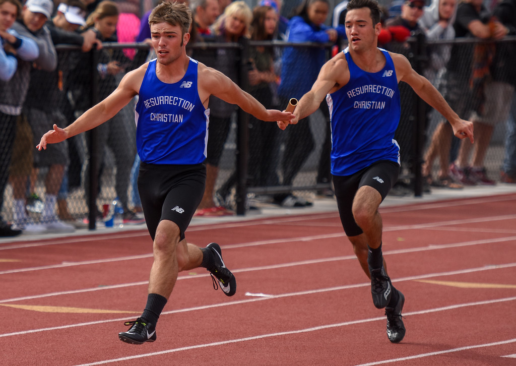 . Resurrection Christian\'s Dalton Armstrong, left, takes a handoff from Colton Stahla during the 2A 4x100-meter relay prelims at the 2018 state track and field meet Friday May 18, 2018 at Jeffco Stadium in Lakewood. (Cris Tiller / Loveland Reporter-Herald)