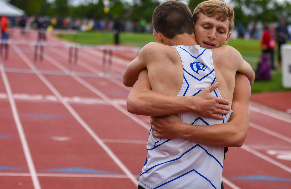 . Resurrection Christian\'s Ben Jackson hugs 2A 300-meter hurdle champion Jacob Yates after finishing second at the 2018 state track and field meet Saturday May 19, 2018 at Jeffco Stadium in Lakewood. (Cris Tiller / Loveland Reporter-Herald)