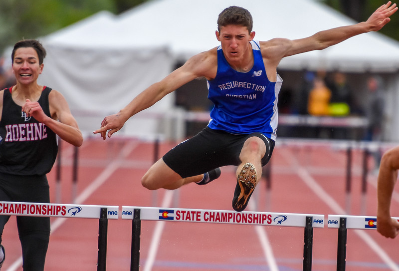 Resurrection Christian's Be Jackson leaps during the 2A 300-meter hurdles at the 2018 state track and field meet Saturday May 19, 2018 at Jeffco Stadium in Lakewood. (Cris Tiller / Loveland Reporter-Herald)