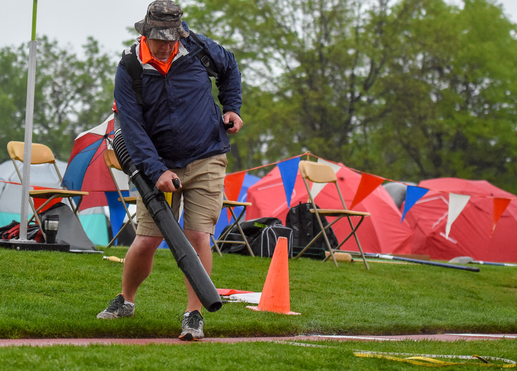 . An official blows the resting water off the jumps track at the 2018 state track and field meet Saturday May 19, 2018 at Jeffco Stadium in Lakewood. (Cris Tiller / Loveland Reporter-Herald)
