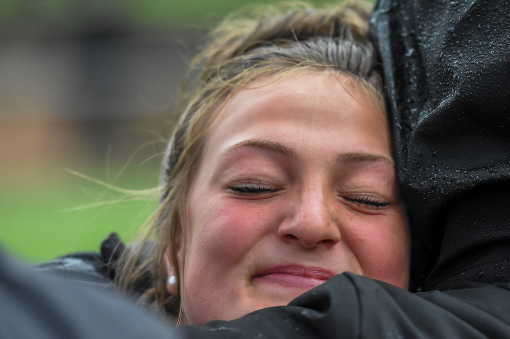 . Loveland\'s Moira Dillow hugs her coach at the 2018 state track and field meet Saturday May 19, 2018 at Jeffco Stadium in Lakewood. (Cris Tiller / Loveland Reporter-Herald)