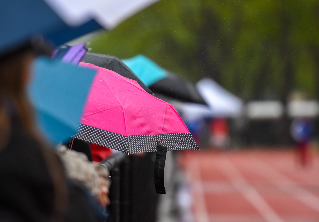 . Spectators line up along the fenceline sheltered under umbrellas at the 2018 state track and field meet Saturday May 19, 2018 at Jeffco Stadium in Lakewood. (Cris Tiller / Loveland Reporter-Herald)