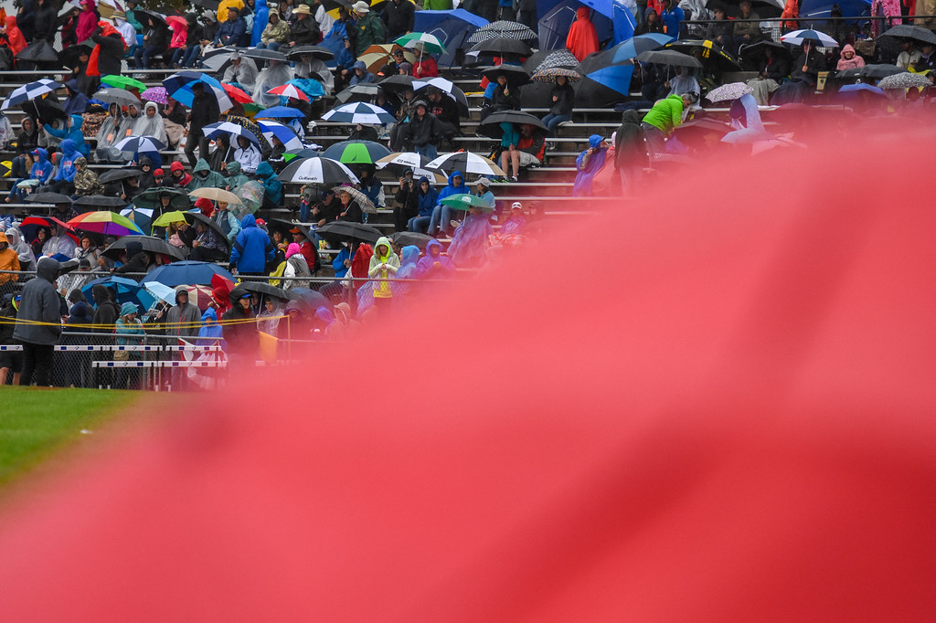 . Spectators look on from the stands under umbrellas at the 2018 state track and field meet Saturday May 19, 2018 at Jeffco Stadium in Lakewood. (Cris Tiller / Loveland Reporter-Herald)