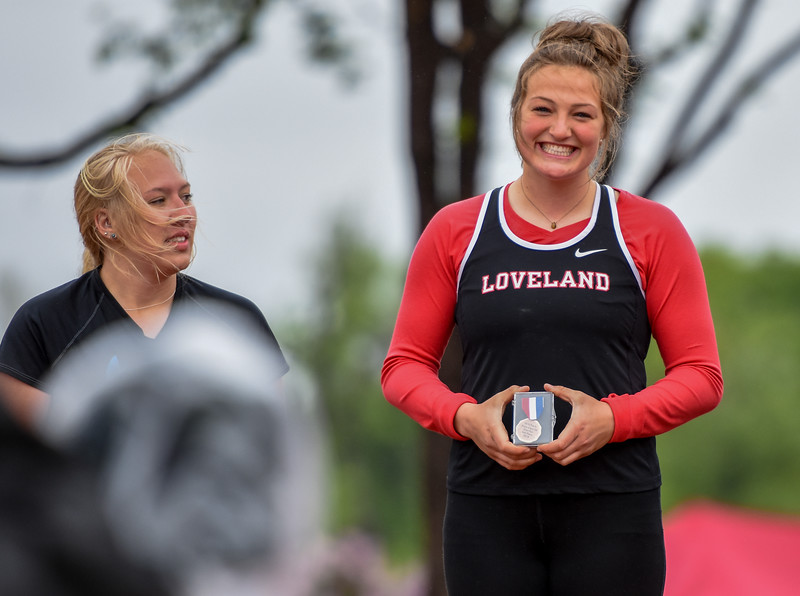 Loveland's Moira Dillow smiles upon receiving her sixth-place shot put medal on the podium at the 2018 state track and field meet Saturday May 19, 2018 at Jeffco Stadium in Lakewood. (Cris Tiller / Loveland Reporter-Herald)