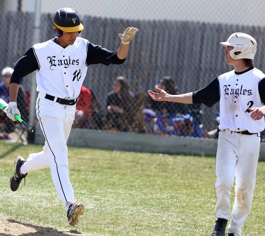 . Thompson Valley\'s Adrian Juarez (10) is congratulated by Seth Dotson (2) after scoring a run against Centaurus on Saturday March 31, 2018 at Constantz Field at TVHS. (Javon Harris / For the Reporter-Herald)