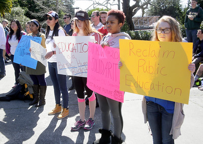 Shaun Walker — The Times-Standard  Students hold signs during a walkout over a statewide tuition increase on the Humboldt State University quad  Wednesday.