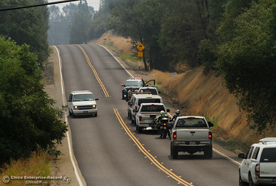 A California Highway Patrol officer stops traffic along the closed Forbestown Road and has them turn around since the road is closed as Cal Fire Butte County and other agencies work to contain the Wall Fire Saturday July 8, 2017 in Oroville, California.  (Emily Bertolino -- Enterprise-Record)