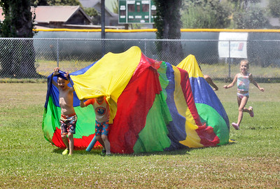Shaun Walker — The Times-Standard  Marky and Kaiser exit a sprinkler-soaked rainbow parachute as children play in the water at Camp Perigot in Blue Lake on Wednesday. The Blue Lake Parks and Recreation summer day camp also features games, arts and crafts, sports, roller skating, theater, field trips, cooking, and gardening.