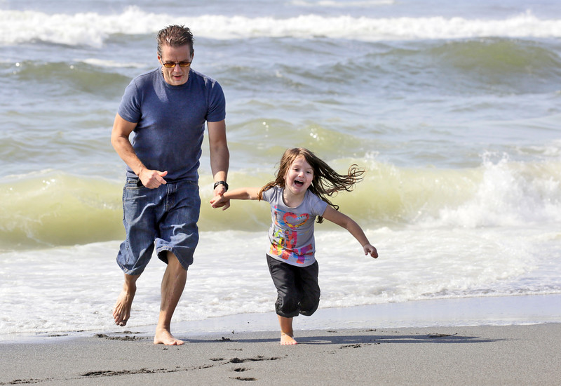 Shaun Walker — The Times-Standard  Stosh Miroth of Weaverville and his daughter Aylaa, 4, play on the edge of the waves at Fairhaven beach Tuesday afternoon as they escape very hot inland weather. Partly sunny and about 72 degrees is expected on the coast for Wednesday, and more hot weather is expected inland.