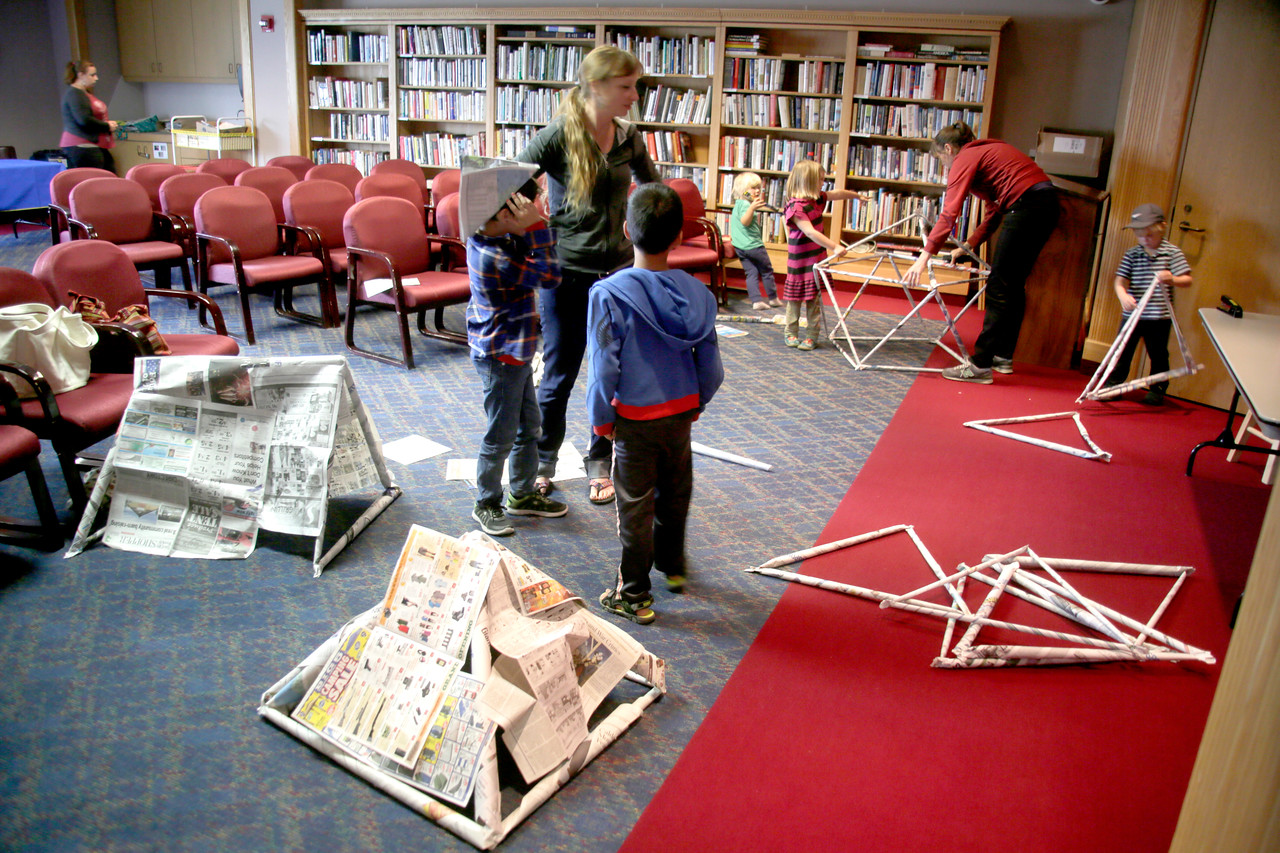 Shaun Walker — The Times-Standard  Children and adults make forts from newspaper at the Eureka library.