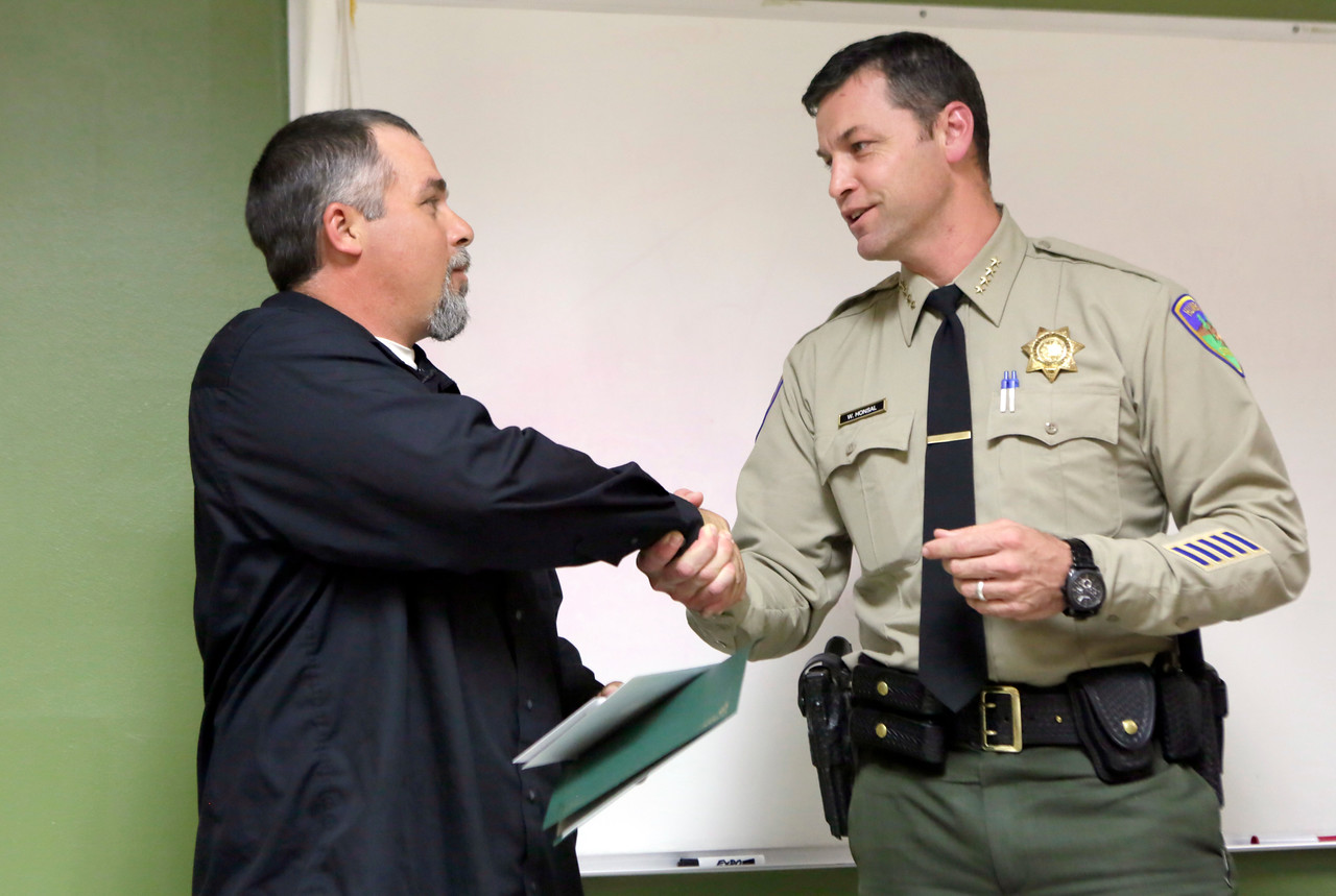 Shaun Walker — The Times-Standard  Humboldt County Sheriff William Honsal gives John Marciel of Eureka an award Thursday for helping to save a girl's life at Centerville Beach last month by restraining her mother, who was assaulting her.