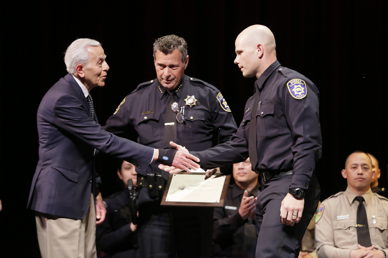 Shaun Walker — The Times-Standard  Trustee Bruce Emad, left, and Eureka Police Chief Andrew Mills, center, give a special award to cadet Joseph Couch at the College of the Redwoods 119th Basic Law Enforcement Academy graduation on Thursday afternoon. Thirty-one cadets graduated. Of those graduating, twenty-four have been hired by various law enforcement departments and others are in different stages of the selection processes.