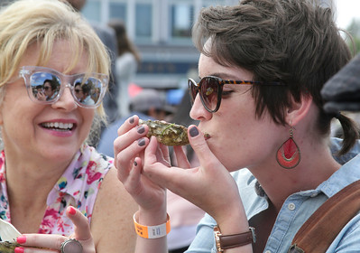 Shaun Walker — The Times-Standard  Michelle Lamarr, left, and Bethany Phelps enjoy oysters at the Oyster Fest on the Arcata Plaza on Saturday.