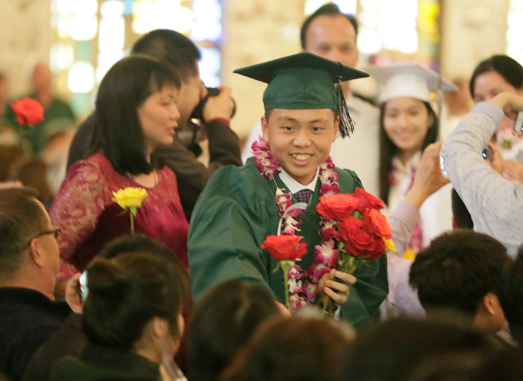. Shaun Walker � The Times-Standard  St. Bernard\'s Academy senior Yuanbin Robin Wu hands out roses at the Eureka school\'s graduation ceremony on Saturday. The private Catholic school graduated 48 students.