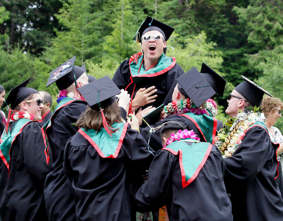 . Shaun Walker � The Times-Standard  Raymond Zhang, top, is mobbed by friends after getting his diploma at Eureka High School\'s graduation ceremony on Friday. The school graduated about 250 seniors in Albee Stadium.