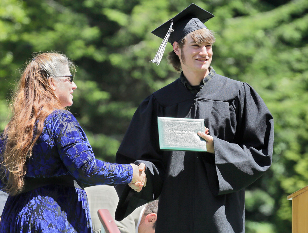 . Shaun Walker � The Times-Standard  Zoe Barnum High School senior Justin Seaman gets his diploma from Eureka City Schools Board of Education President Lisa Olliver during a ceremony in Eureka High School\'s Albee Stadium on Wednesday afternoon. About 40 students graduated.