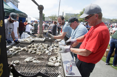 Shaun Walker — The Times-Standard  Michael Scott, right, helps shuck oysters at the Eureka High Cheer booth on Saturday.