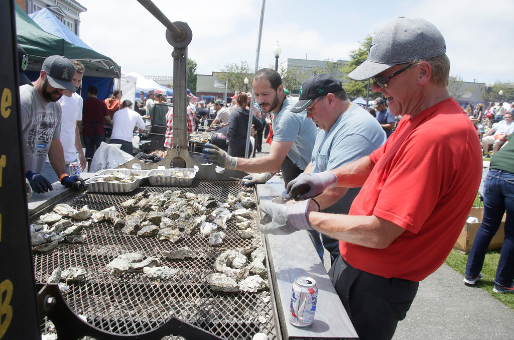 . Shaun Walker � The Times-Standard  Michael Scott, right, helps shuck oysters at the Eureka High Cheer booth on Saturday.
