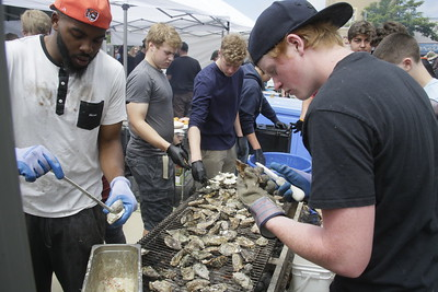Shaun Walker — The Times-Standard  Arcata High School students Jordan Briggs, left, and Tri Jensen shuck oysters for Mazotti's at the Oyster Fest on the Arcata Plaza on Saturday.