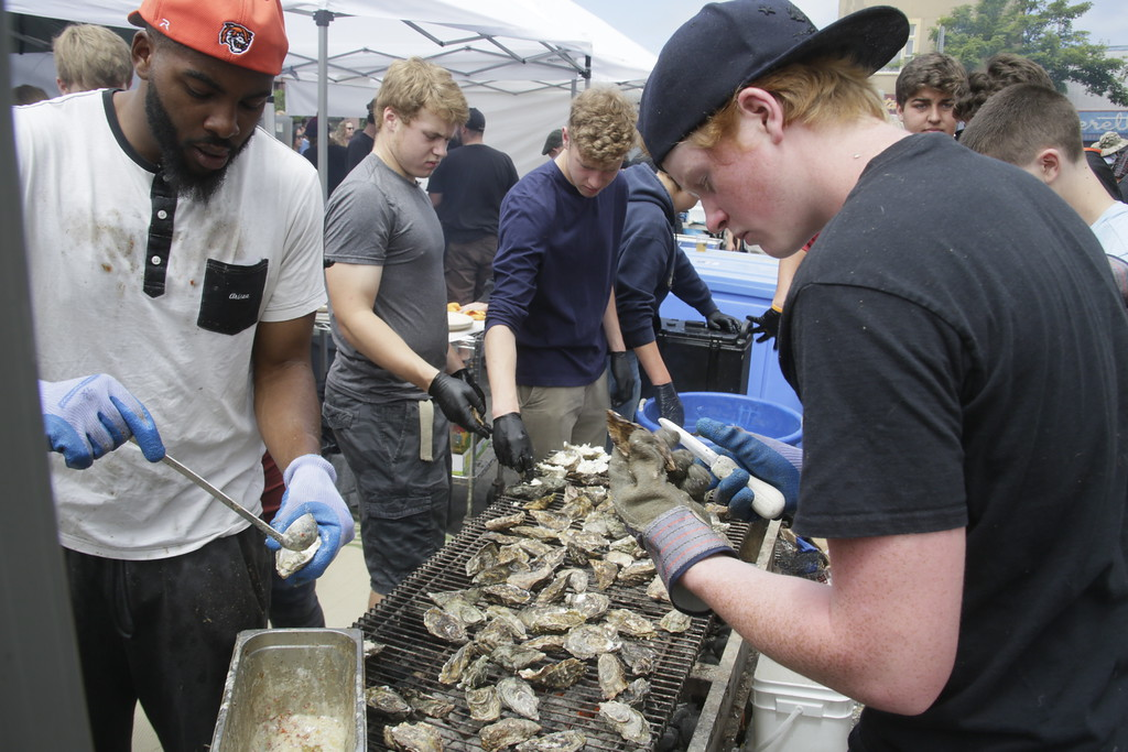 . Shaun Walker � The Times-Standard  Arcata High School students Jordan Briggs, left, and Tri Jensen shuck oysters for Mazotti\'s at the Oyster Fest on the Arcata Plaza on Saturday.