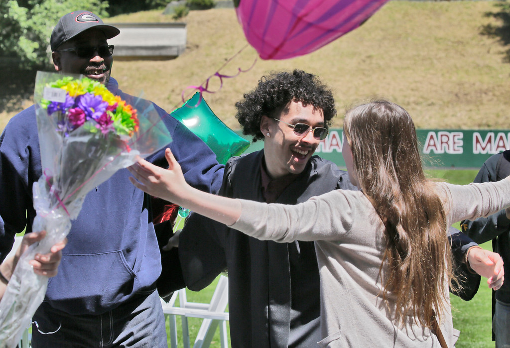 . Shaun Walker � The Times-Standard  Zoe Barnum High School graduate Shane Harris reaches to hug his cousin Grace Hayes, 14, of Eureka as his grandfather Anthony Sherrod looks on after a ceremony at Eureka High School\'s Albee Stadium on Wednesday afternoon. About 40 students graduated.