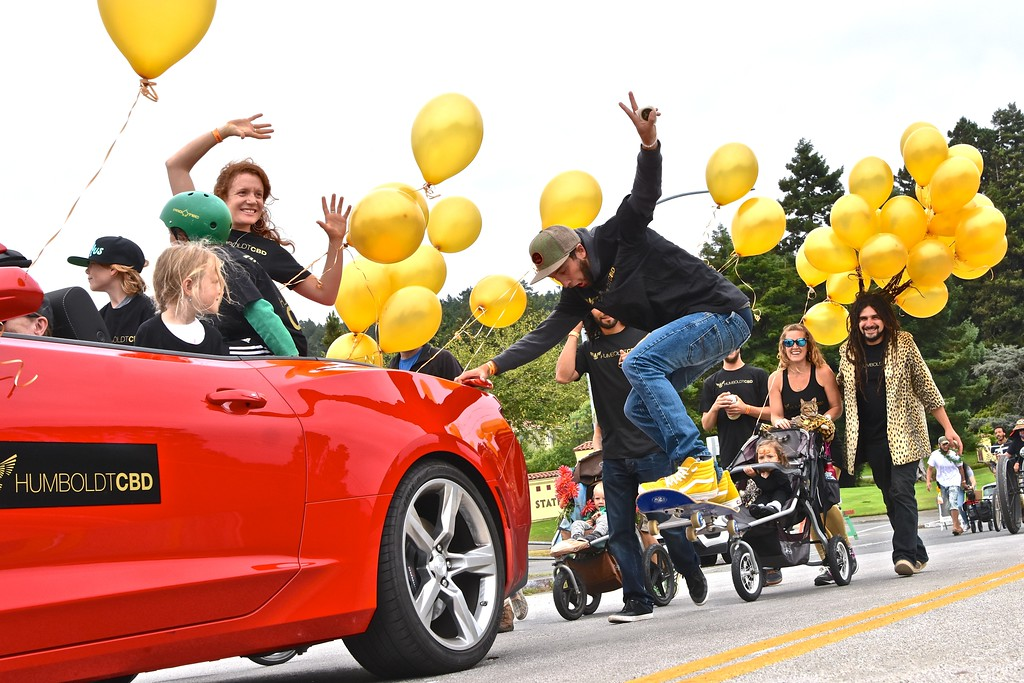 . Clay Adams gets high catching air with his skateboard with the Humboldt CBD float. The dreaded balloon hairdo in the background is worn by Avishai Bombaklat of Humboldt CBD. José Quezada�For the Times-Standard