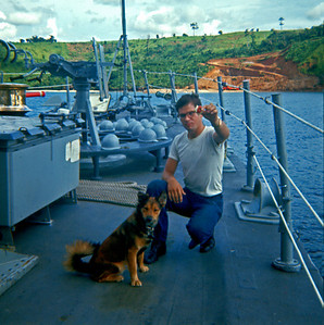 Commodore, our ship mascot, came on board as a puppy at San Diego, probably January 1969 (We left the states in February). Here he is shown with RM3 Eden trying to teach him tricks. (Bininga Bay, PI, 1969)