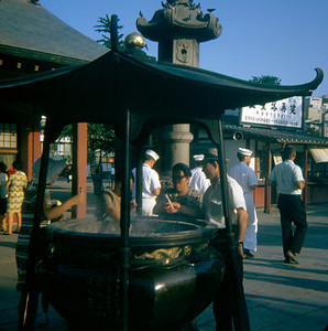 """Outside the temple is this """"Holy Smoke"""" said to heal those who touch it. (Tokyo, Japan August 1969)"""