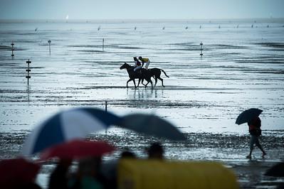 COURSES :  ARRIVEE, TROT, PARAPLUIE, ILLUSTRATION - COURSES SUR LA PLAGE DE CUXHANEN/DUHNER - 18/08/13 - PHOTO CHRISTOPHE BRICOT -  DUHNEN Mudflat Courses à Cuxhaven Le parc national de la mer des Wadden de Hambourg n'est pas seulement un site du patrimoine mondial de l'UNESCO, mais il est aussi le lieu pour ce qui doit sûrement être l'une des courses de chevaux les plus étranges du monde: les Duhnen Mudflat Courses près de Cuxhaven. Dans le contexte dramatique de l'estuaire de l'Elbe, une voie de navigation internationale, les chevaux et leurs jockeys participer à des courses à travers les vasières détenus à marée basse. Les visiteurs peuvent observer ce spectacle remarquable se dérouler à partir de la digue à proximité.
