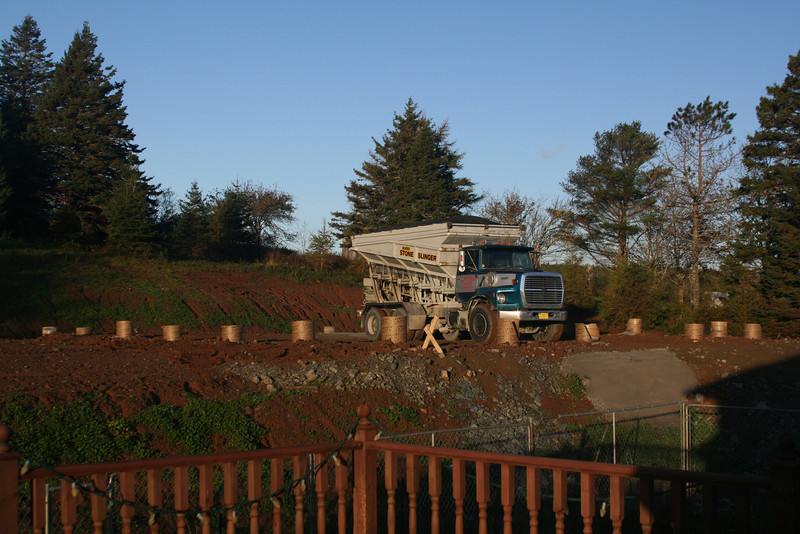 Morning, Day 6 (Oct 22, 2010). View from my deck.  Yesterday, Day 5, was site prep, but since that job-thing got in the way, I missed getting the pic. Slinger truck (at 8 am!) with the first of 3 loads of Class A gravel used to set the base for the floor.