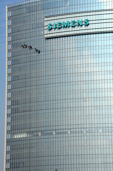 Window cleaners suspended on the tower of the Siemans building in Beijing in the People's Republic of China.