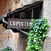 "The rustic sign ""Copisteria"" likely advertises a copying office, beside the Church of Santa Cecilia, Bologna."
