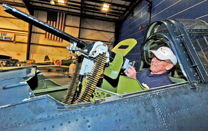 """Dixie Wing's Lonnie Webster shows an original .50 Calibre Machine Gun mounted in the rear cockpit of the """"Dauntless Dive Bomber"""". This """"Dauntless"""" is the last surviving Dauntless in the world to hold a flight certification.<br /> <br /> This SBD is a movie star! If you want to see this """"Dauntless"""" SBD-5 in action, watch the film """"Midway,"""" or rent the blockbuster mini-series """"The Winds of War"""" and its sequel, """"War and Remembrance."""""""