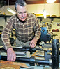 Dixie Wing's Col. Jon Wilson assembles a replica machine gun that will fit on one of the WWII aircraft on display