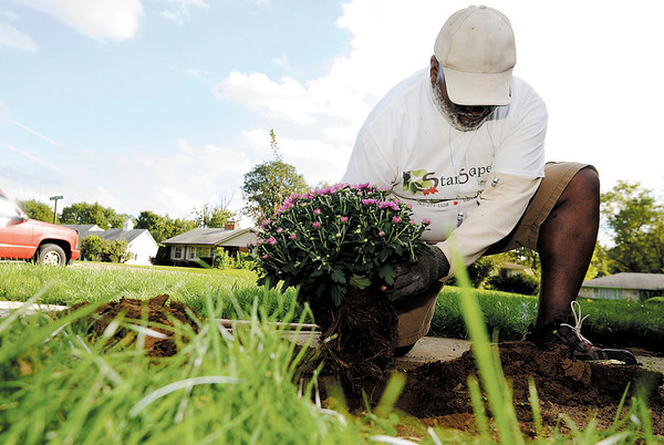 Don Knight   The Herald Bulletin<br /> Stan Barclay plants a mum in a new flower garden. Barclay stays physically active with his landscaping company StanScapes.