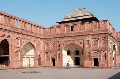 Cour intérieure dans le Fort Rouge d'Agra construit par Akbar. C'est un palais résidentiel pour son fils Jahângîr. À partir de ce moment-là, le fort n'est plus seulement une place militaire mais aussi un lieu de résidence. La construction du Fort, en grès rouge, commença en 1565, et s'acheva en 1571, sous le règne de Shah Jahan, petit-fils d'Akbar. Il marque la naissance du style impérial moghol, fusion de l'art perse du XVème siècle et de la tradition architecturale hindo-musulmane prémoghole. Le Fort d'Agra est impressionnant. A l'intérieur de ses murailles ont été édifiés plusieurs palais et mosquées, de grès rouge et marbre blanc. C'est un véritable labyrinthe de bâtiments qui forme une petite ville dans la ville. Ces monuments abritaient en leur temps des chambres, des halls de réception privés et publics, des appartements d'été et d'hiver ainsi que des lieux de prière.