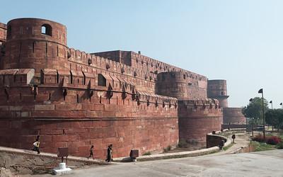 Fort Rouge d'Agra construit par Akbar. C'est un palais résidentiel pour son fils Jahângîr. À partir de ce moment-là, le fort n'est plus seulement une place militaire mais aussi un lieu de résidence. La construction du Fort, en grès rouge, commença en 1565, et s'acheva en 1571, sous le règne de Shah Jahan, petit-fils d'Akbar. Il marque la naissance du style impérial moghol, fusion de l'art perse du XVème siècle et de la tradition architecturale hindo-musulmane prémoghole. Le Fort d'Agra est impressionnant : non seulement il mesure 2.4 km de circonférence, mais en plus c'est une forteresse entourée d'une double enceinte. Un fossé large de 9 m et profond de 11m sépare le mur extérieur, haut de 12 m, de l'enceinte intérieure, haute de 21 m. A l'intérieur de ces murailles ont été édifiés plusieurs palais et mosquées, de grès rouge et marbre blanc. C'est un véritable labyrinthe de bâtiments qui forme une petite ville dans la ville. Ces monuments abritaient en leur temps des chambres, des halls de réception privés et publics, des appartements d'été et d'hiver ainsi que des lieux de prière.