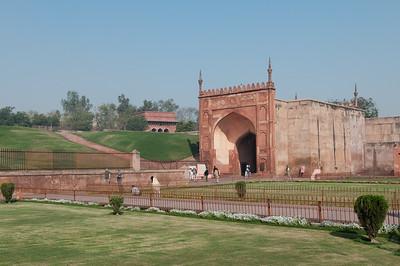 Amar Singh Gate (Porte de Lahore en grès rouge, ainsi nommée parce qu'elle fait face à Lahore , maintenant au Pakistan ) au Fort Rouge d'Âgrâ, construit par Akbar. C'est un palais résidentiel pour son fils Jahângîr. À partir de ce moment-là, le fort n'est plus seulement une place militaire mais aussi un lieu de résidence. La construction du Fort, en grès rouge, commença en 1565, et s'acheva en 1571, sous le règne de Shah Jahan, petit-fils d'Akbar. Il marque la naissance du style impérial moghol, fusion de l'art perse du XVème siècle et de la tradition architecturale hindo-musulmane prémoghole. Le Fort d'Agra est impressionnant : non seulement il mesure 2.4 km de circonférence, mais en plus c'est une forteresse entourée d'une double enceinte. Un fossé large de 9 m et profond de 11m sépare le mur extérieur, haut de 12 m, de l'enceinte intérieure, haute de 21 m. A l'intérieur de ces murailles ont été édifiés plusieurs palais et mosquées, de grès rouge et marbre blanc. C'est un véritable labyrinthe de bâtiments qui forme une petite ville dans la ville. Ces monuments abritaient en leur temps des chambres, des halls de réception privés et publics, des appartements d'été et d'hiver ainsi que des lieux de prière.