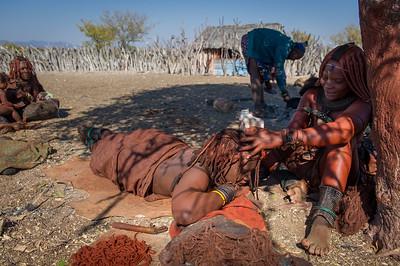 Preparing a Himba woman long dreadlocks
